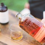 A bottle of Bulleit® Bourbon and a glass with a shot of bourbon